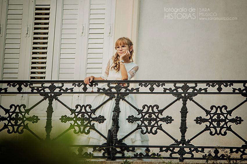 Reportaje de comunion niña vestida con traje de comunion en balcon asomada