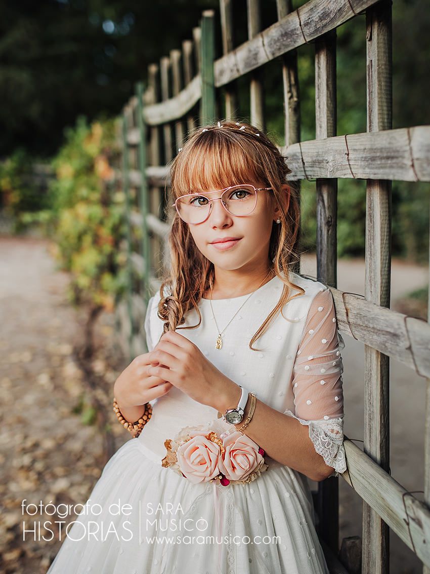 Reportajes comunion niña apoyada en verja en Book de Comunion en Jardin del Capricho